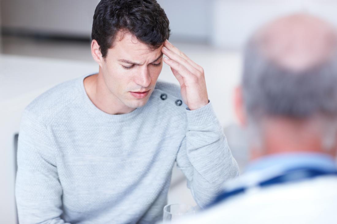 片頭痛について医者に話す苦痛に頭を抱えている男。