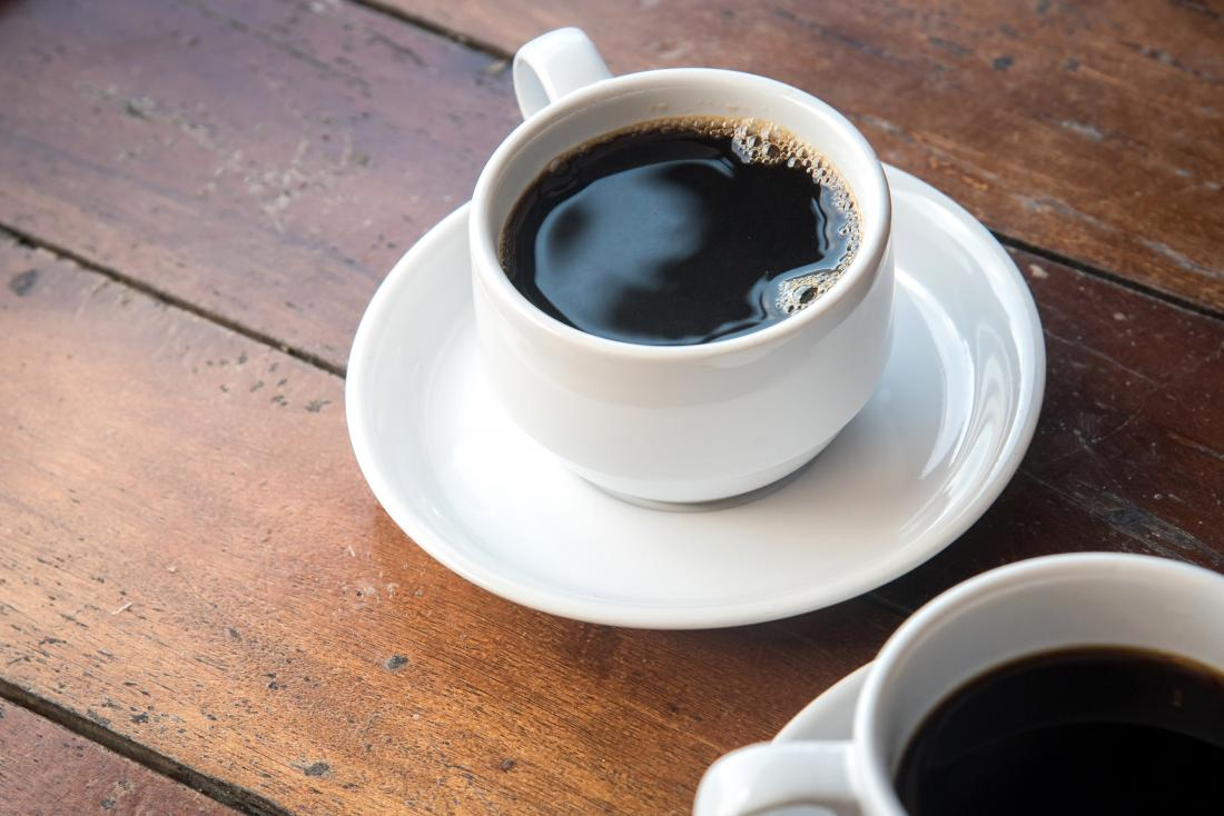 Черно кафе в чаши и чинии на дървена маса.