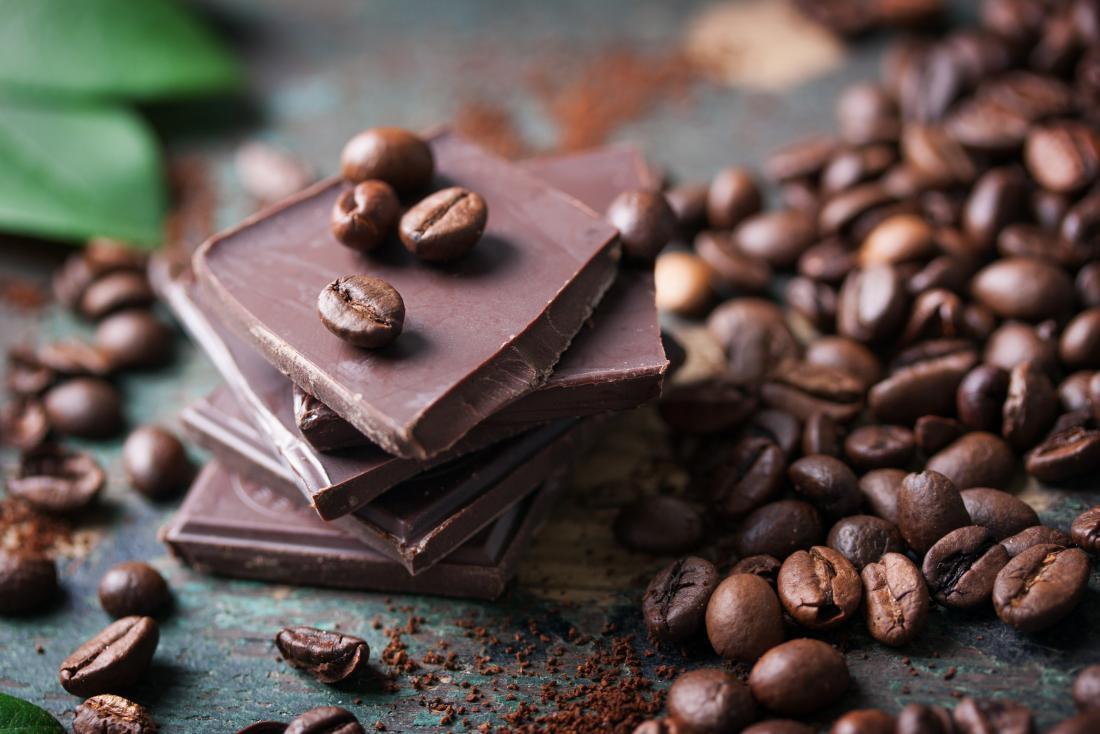 Части от тъмен шоколад, заобиколени от кафе на зърна.