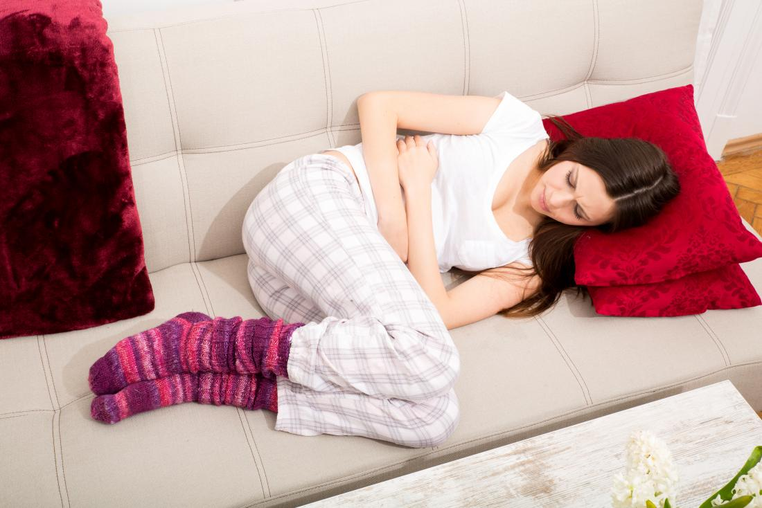 jeune femme sur le canapé souffrant de douleurs à l'estomac