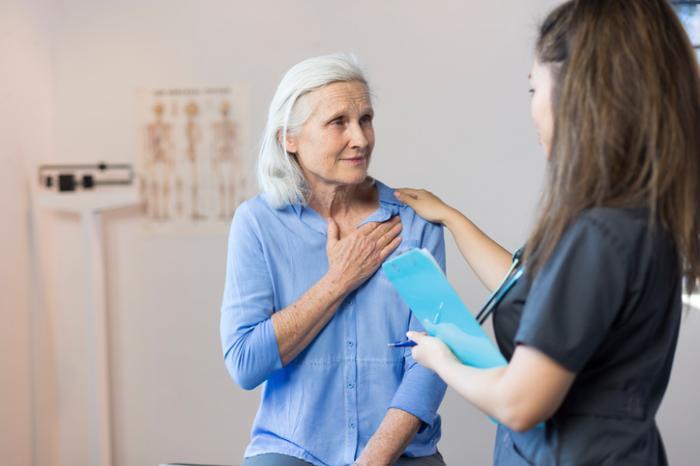 [ältere Patientin zeigt der jungen Krankenschwester eine Brustschmerzen]