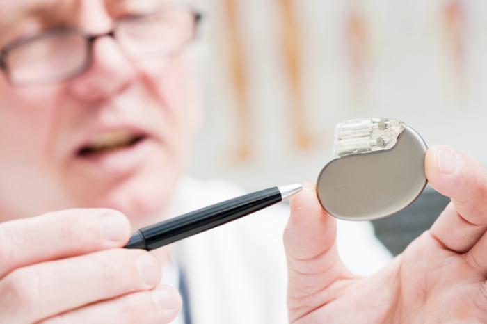 [älterer männlicher Arzt zeigt auf einen Herzschrittmacher mit einem Stift]