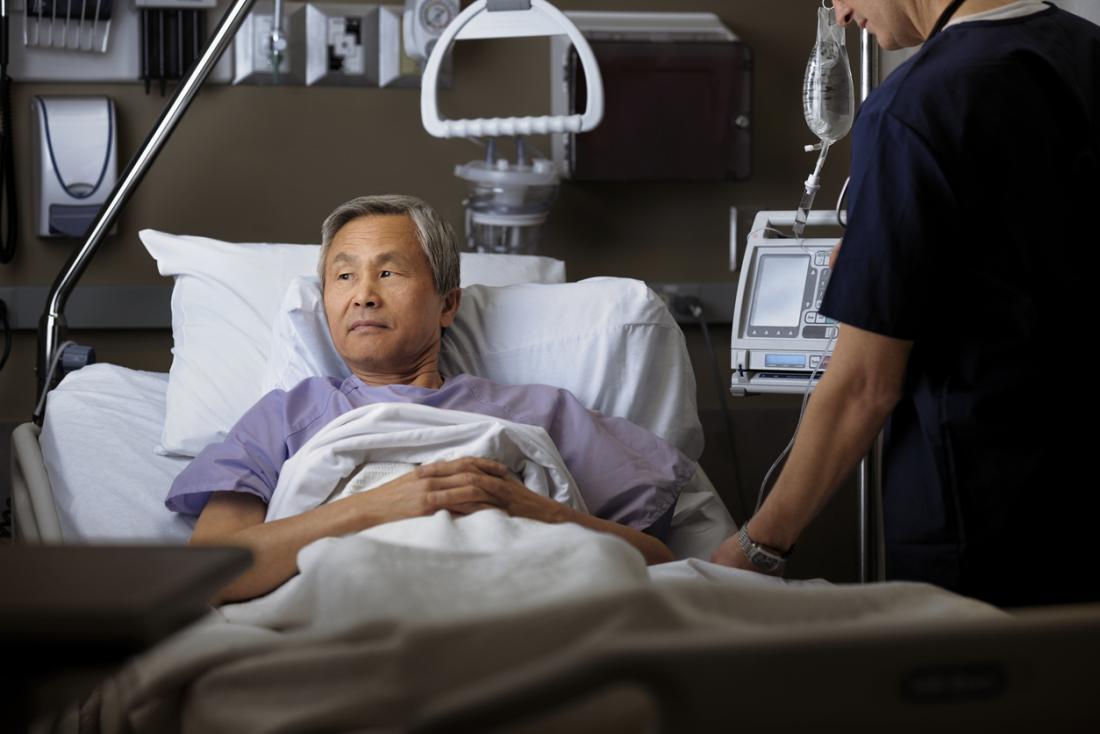 [l'uomo si sta riprendendo da un intervento chirurgico in un letto d'ospedale]