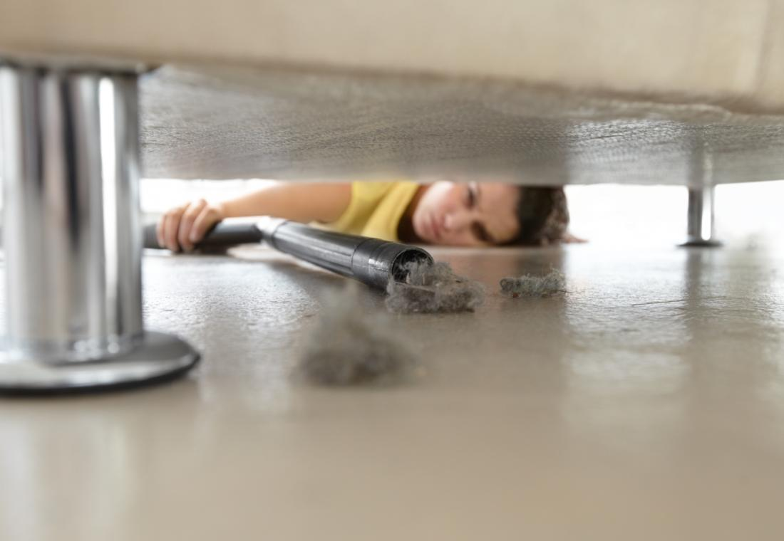 Donna aspirapolvere sotto il suo divano