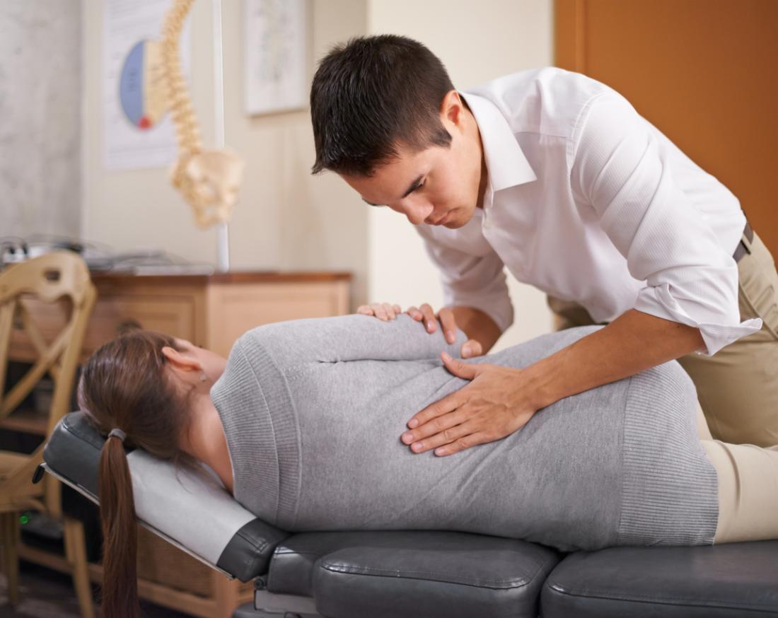 Chiropraktiker, der den Rücken einer Dame manipuliert