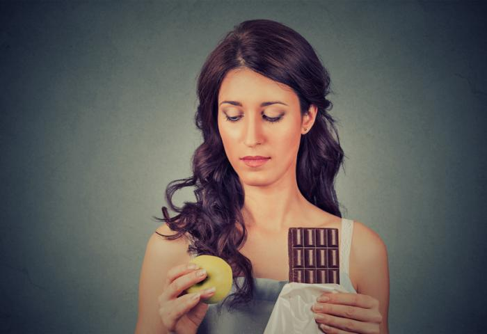 Một người phụ nữ chọn giữa sô cô la và một quả táo.