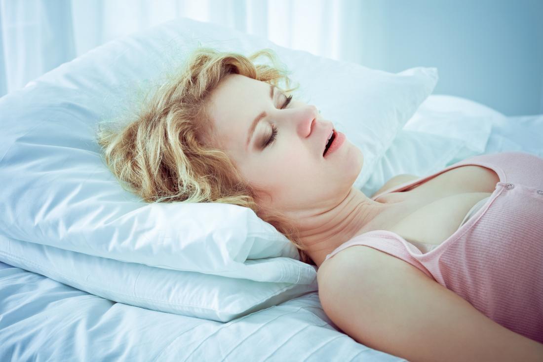 Femme essayant de ronfler les remèdes maison tout en dormant sur le lit.
