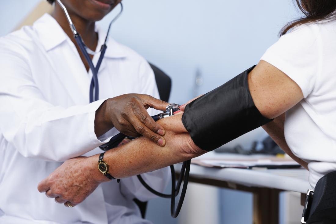 médico levando pacientes do sexo feminino a pressão arterial