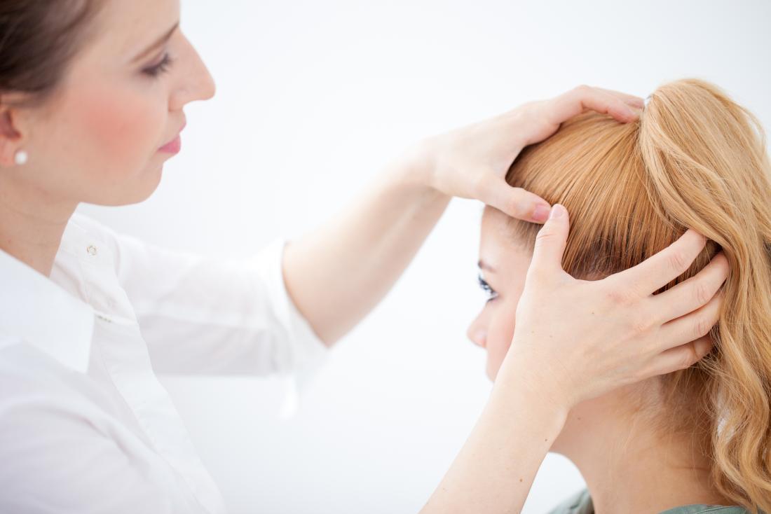Doktor, der das Haar eines Patienten für Pilarzyste kontrolliert