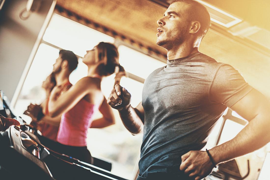 Homme exerce sur tapis roulant dans la salle de gym.