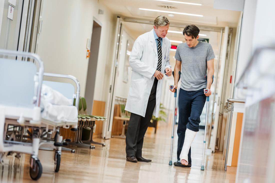 Paciente com a perna quebrada no elenco de muletas, com médico no hospital.
