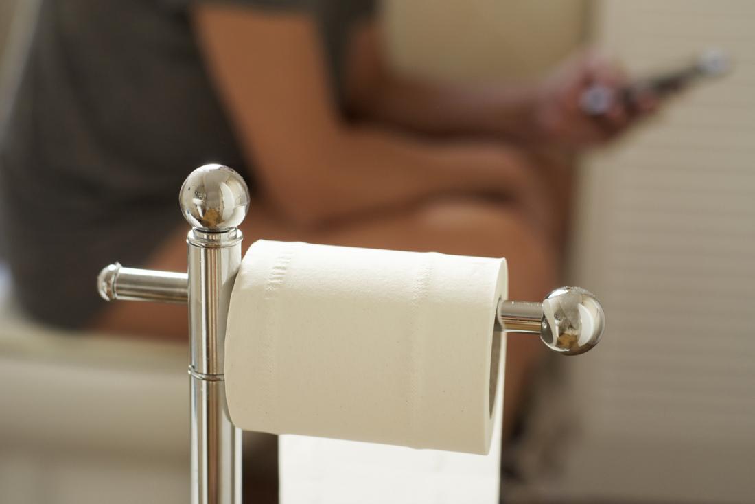 човек, седнал на тоалетната, използвайки телефона си