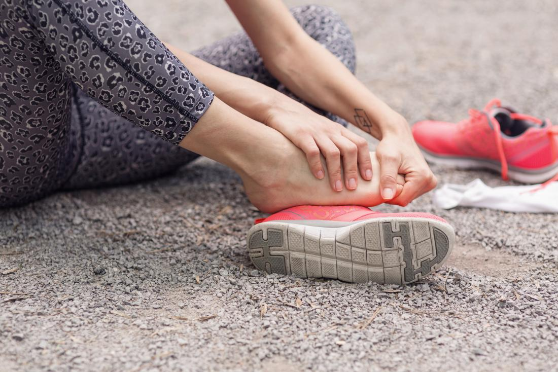 彼女の靴と靴下を脱いで痛みで彼女の足につけているテーラーのバニオンを持つ女性。
