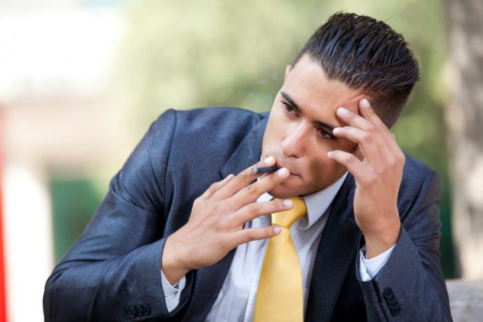 [Mann in einem Anzug, der beim Rauchen beunruhigt aussieht]