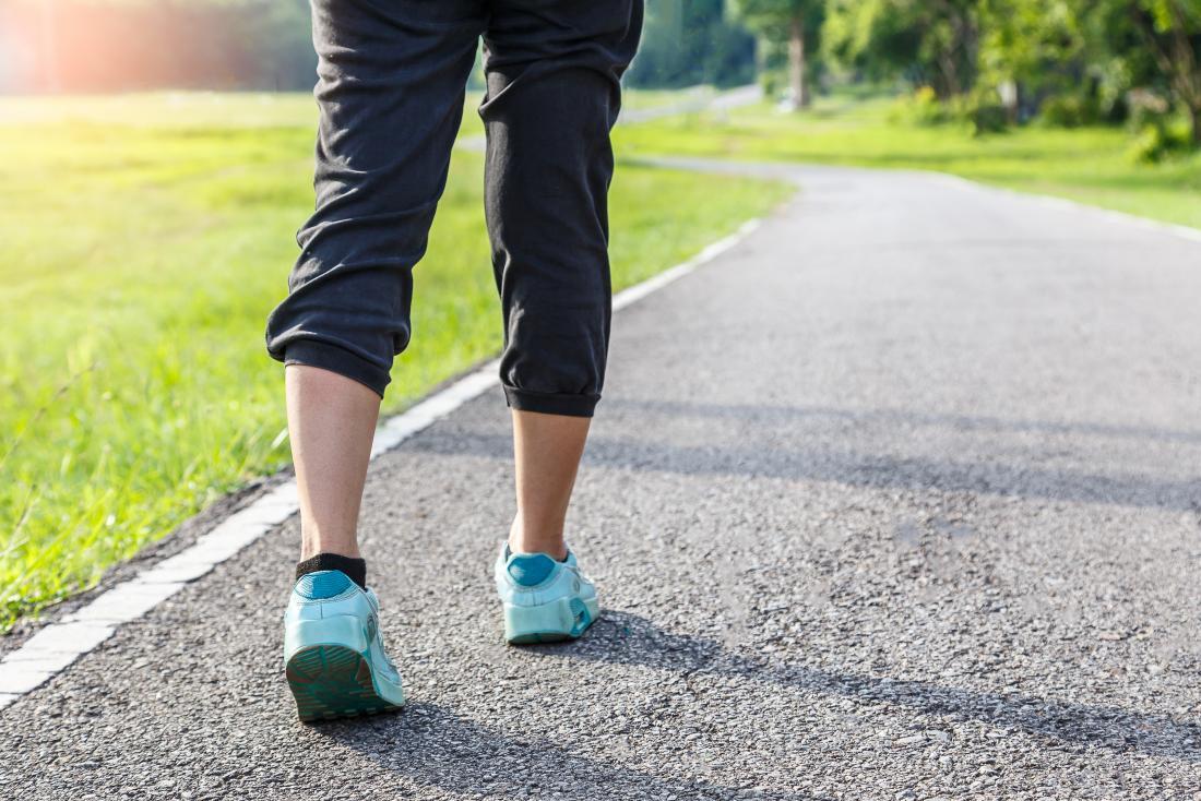Personne qui marche avec une démarche régulière autour de la piste de course à l'extérieur dans des vêtements de sport.