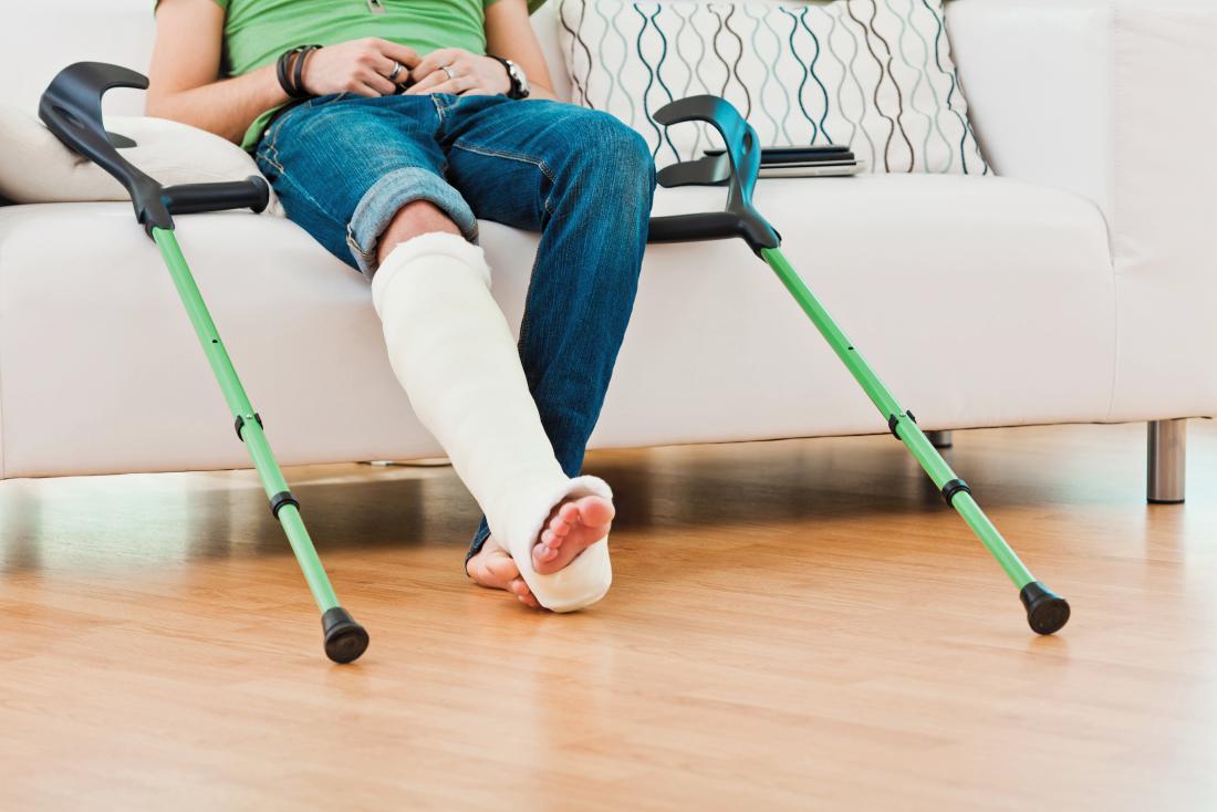 Personne assise sur un canapé avec des béquilles et une jambe cassée en fonte.