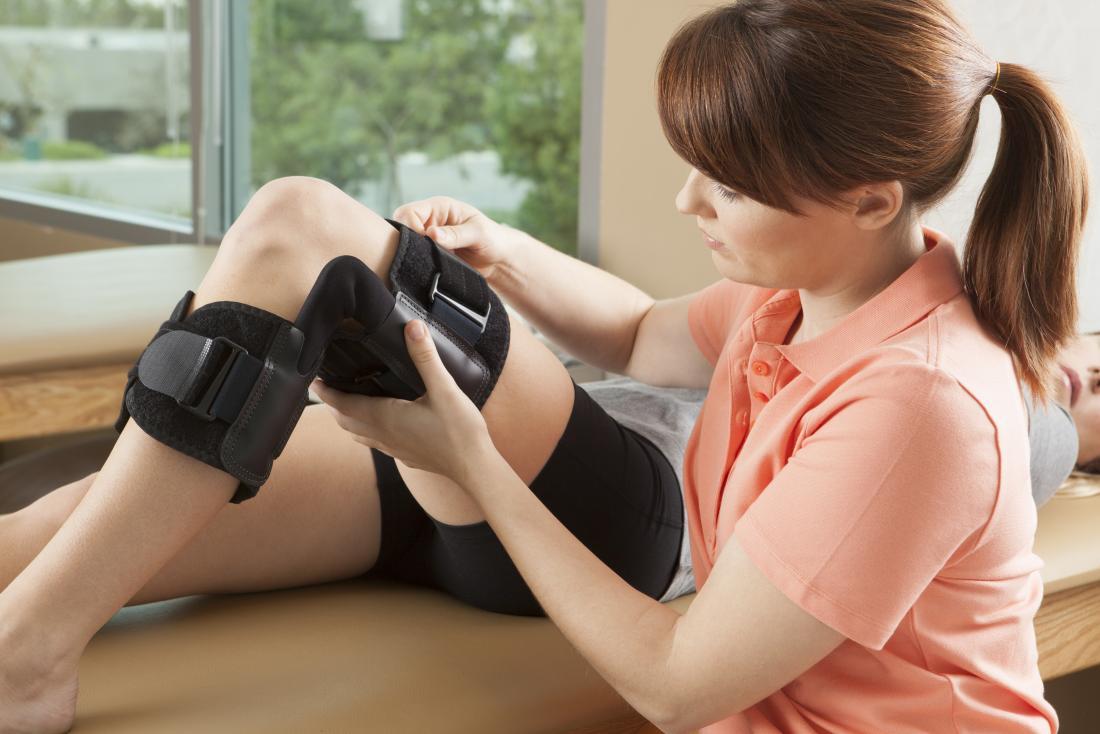 Personne recevant une orthèse de genou et de jambe formant un physiothérapeute.