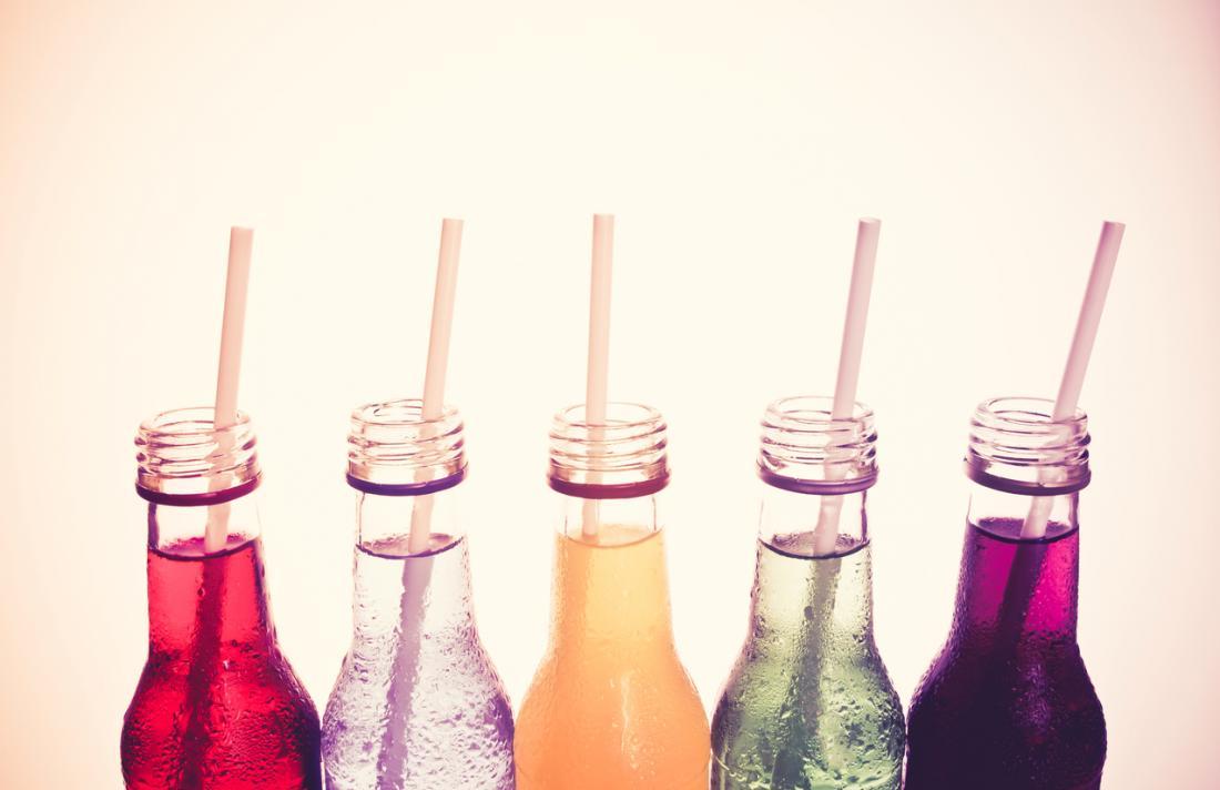 Bouteilles de boissons gazeuses avec des pailles.