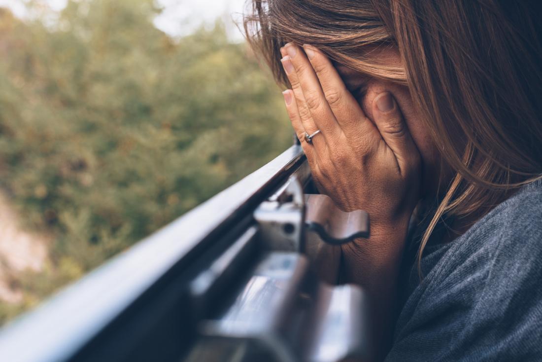 Mulher triste, cobrindo o rosto com as mãos.