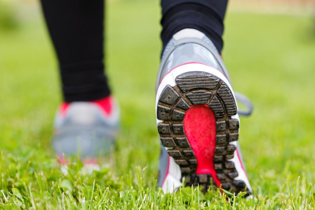 Лице ходене в спортни обувки над трева.
