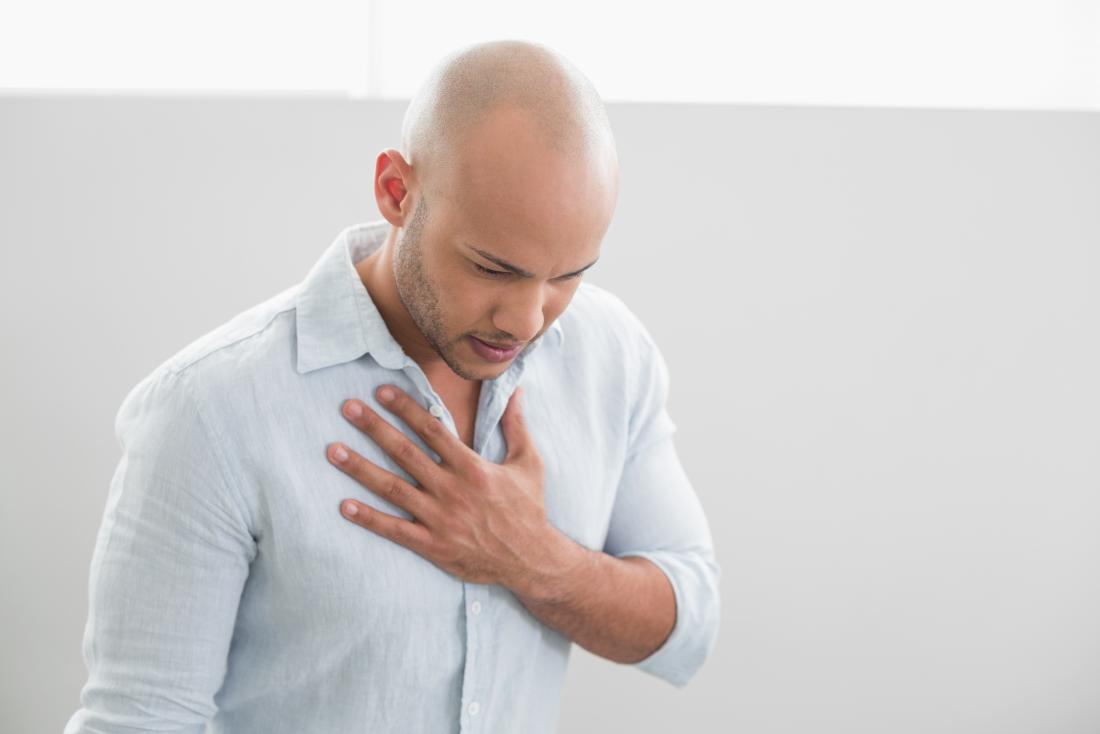 L'uomo stringe il petto a causa del dolore al bruciore di stomaco.
