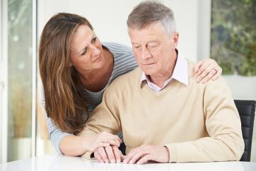 homem idoso confuso sendo consolado pela filha