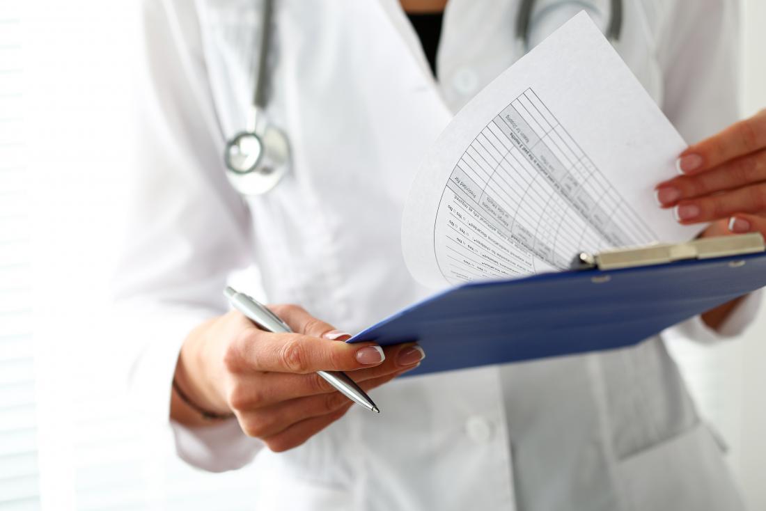 Doktor, der medizinisches Klemmbrett betrachtet, um anasarca zu bestimmen