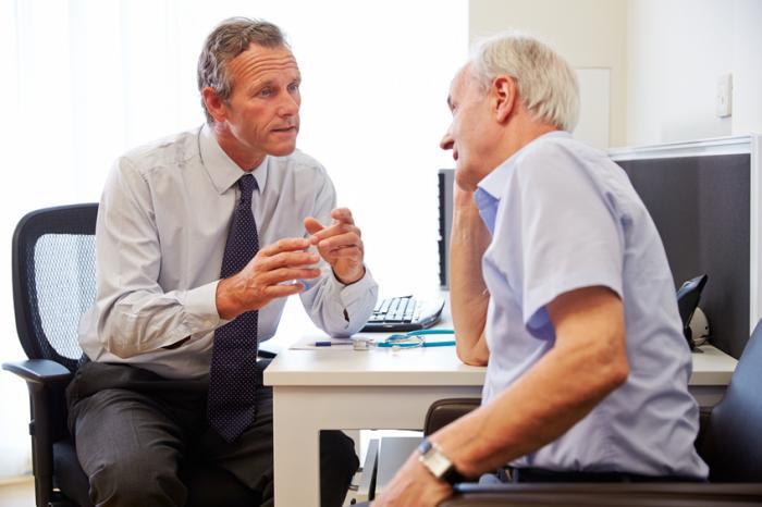 Doktor in Rücksprache mit älterem männlichem Patienten