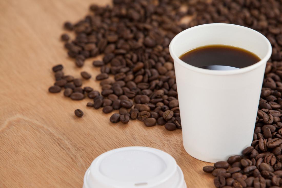 Tasse à café à emporter entourée de grains de café.