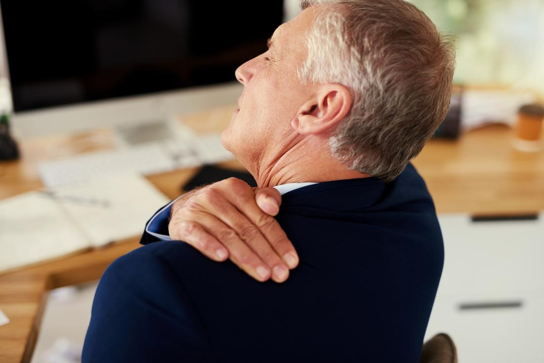 Uomo d'affari con borsite della spalla che tiene in cima alla spalla e torna nel dolore, seduto alla scrivania al lavoro.