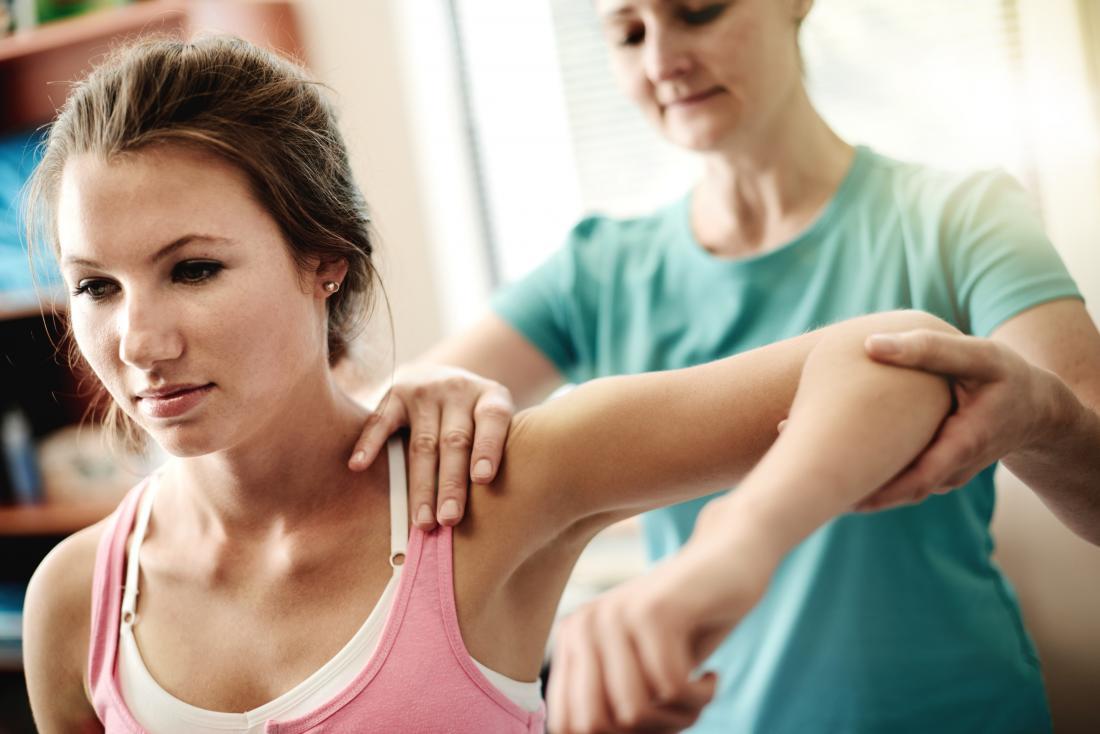 Mulher que recebe a fisioterapia para tratar ferimento do ombro e do braço.