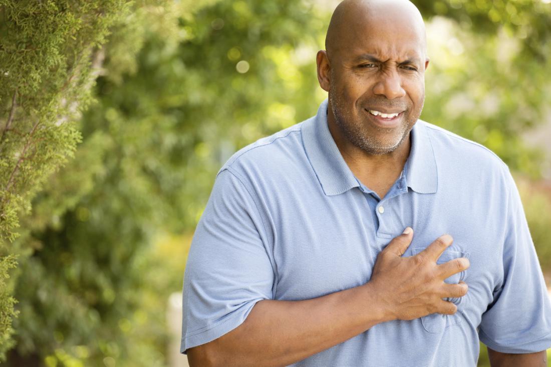 Mann, der Schmerz erfährt und seine Brust hält.