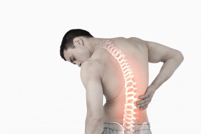 Un uomo con la colonna vertebrale visibile tiene le spalle.