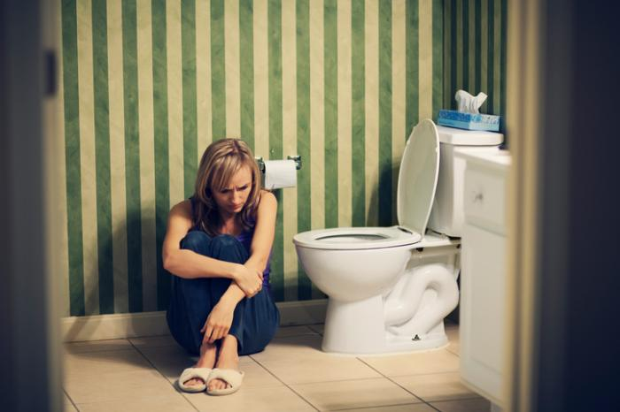 女性がトイレに座っている