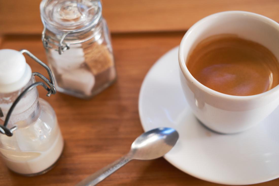 ミルクと砂糖のキューブとコーヒーのカップ。