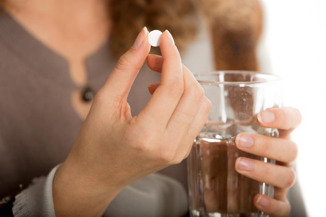 Mulher tomando pílula de medicação, com um copo de água.