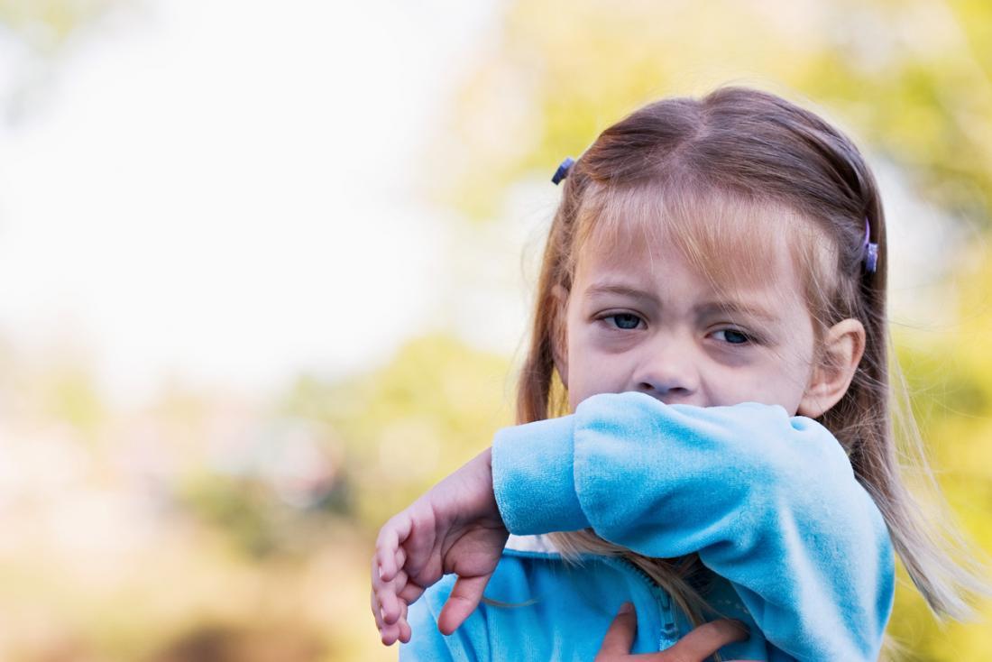 Kind hustet in Ellenbogen