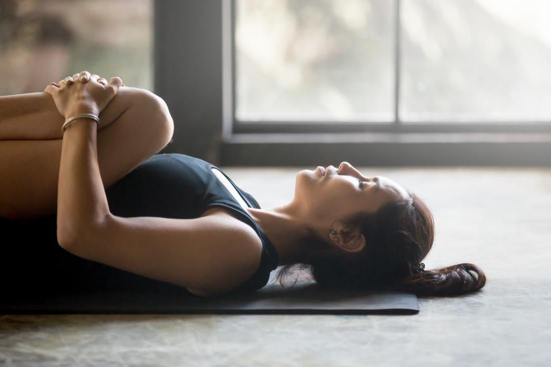 mulher deitada com os joelhos dobrados, abraçando-os ao peito na pose de ioga Apanasana