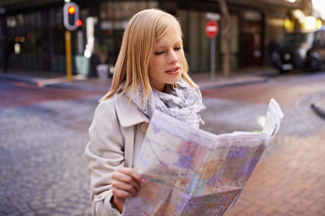 Người phụ nữ cố gắng để đọc bản đồ, bị mất trong thành phố.