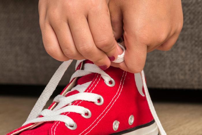 Младо момиче, което облича обувки