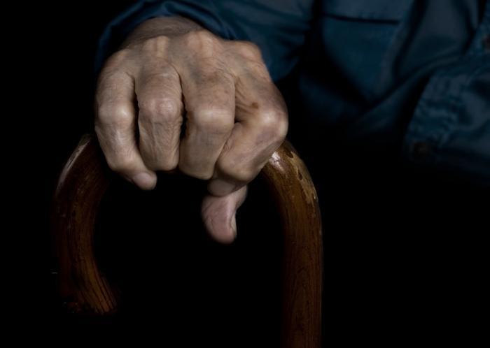 [Main de l'homme âgé tenant le bâton de marche]