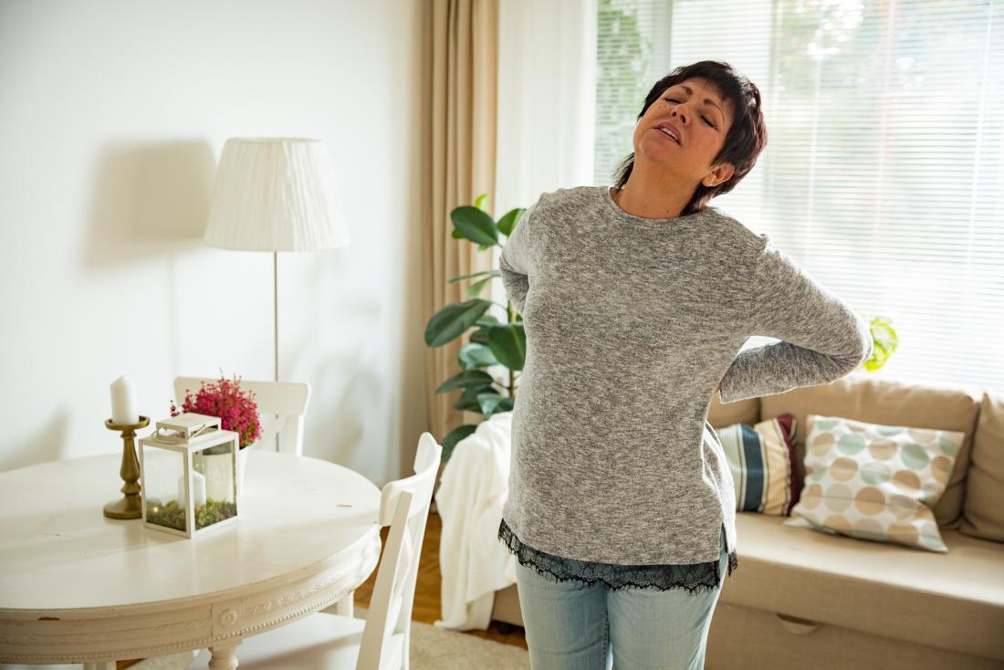 femme mature avec des douleurs au bas du dos