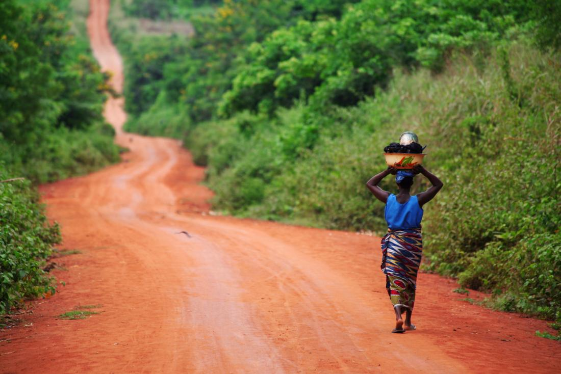 Femme africaine marchant le long d'un chemin de terre.