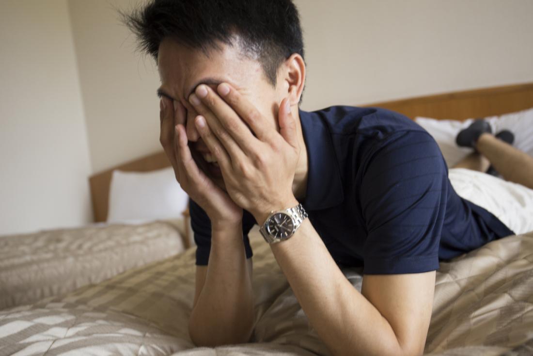 彼の目を彼の手で覆っているベッドの上に胃の上に横たわっている男