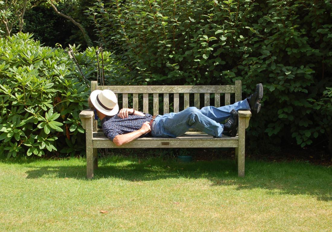 homem tendo sesta em um banco na sombra