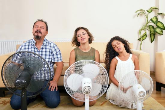 Família sentada na frente de fãs oscilantes para se refrescar