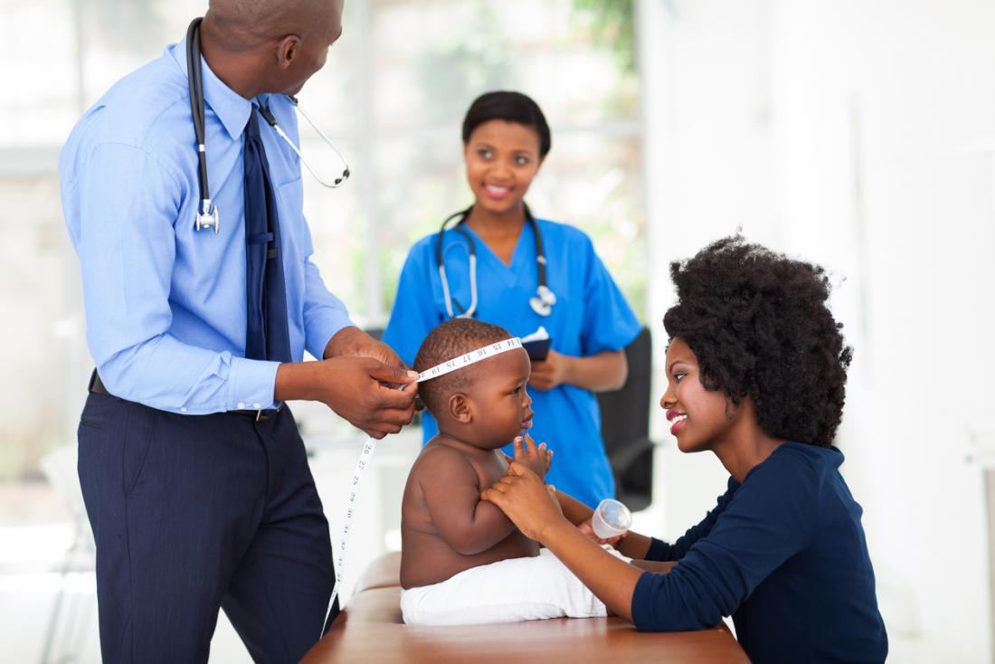 Bébé ayant sa tête mesurée par un pédiatre.