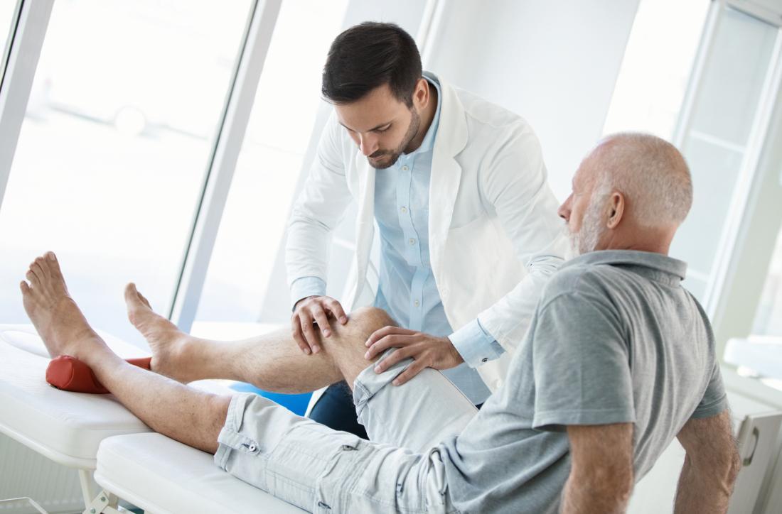 Uomo anziano con la sindrome della fascia ileotibiale che ha il ginocchio controllato dal medico durante la terapia fisica.