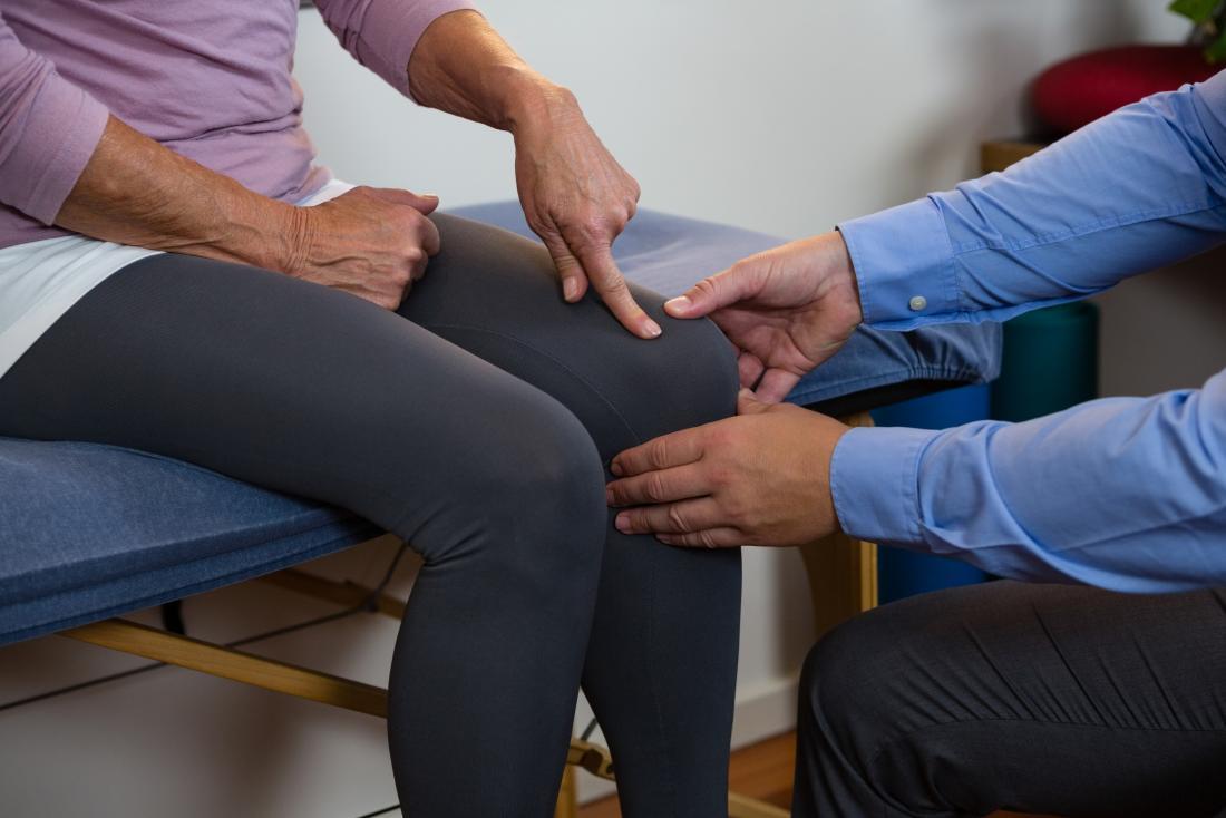 Donna che indica al problema con il suo ginocchio mentre sedendosi sul letto di terapia fisica.