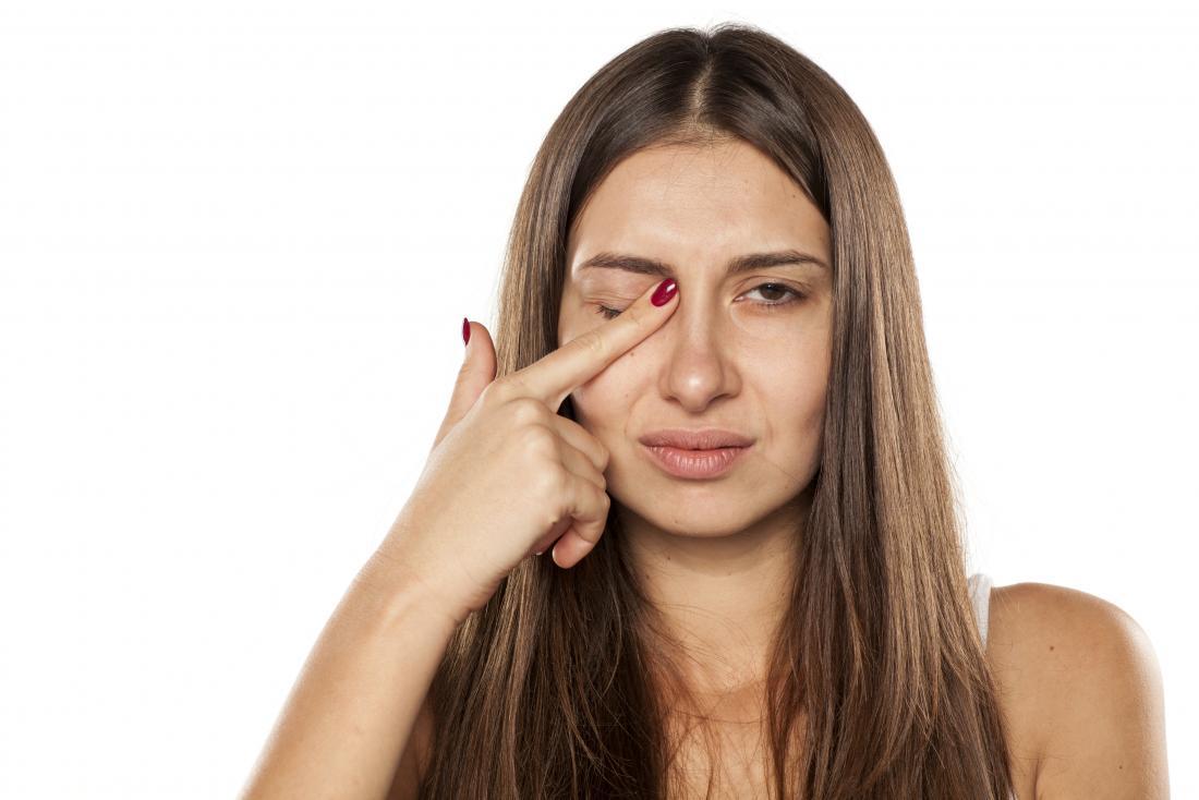 mulher tocando seu olho